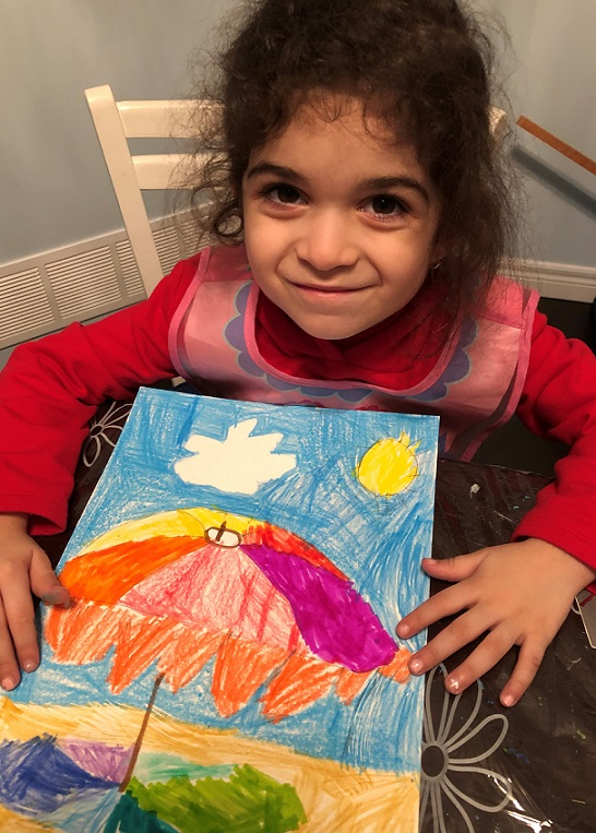 Young girl posing with her completed drawing of coloured umbrella.